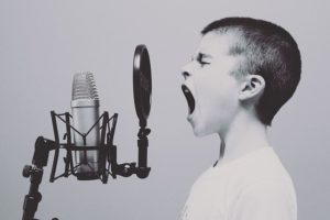child yelling into microphone